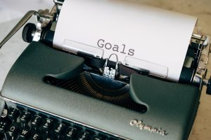 """old typewriter with a piece of paper in it with """"goals"""" typed on the paper"""